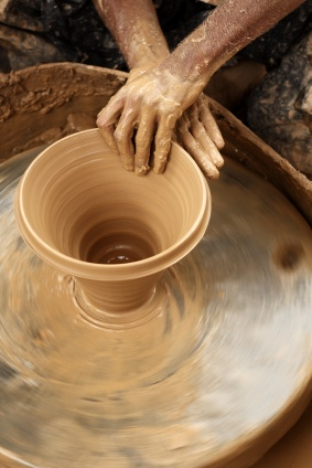 A potter is crafting plant pots with clay.